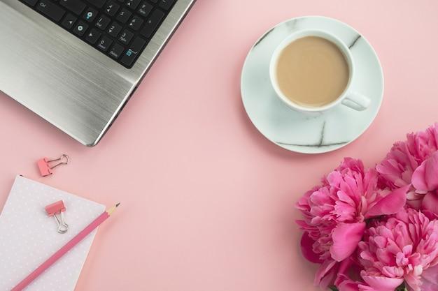 Biurowy stół różowy. miejsce pracy z laptopem, notatnikiem, kwiatami piwonii i kawą