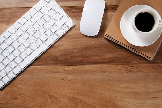 Biurowy stół z notatnikiem, komputerem i filiżanką kawy.