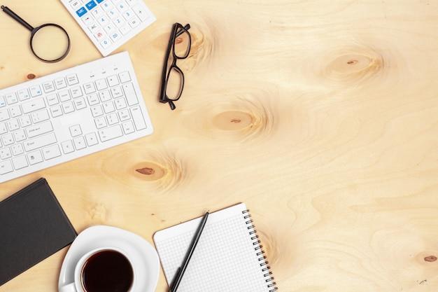 Biurowy stół z nutowym papierem, klawiaturą komputerową i materiałami z bliska