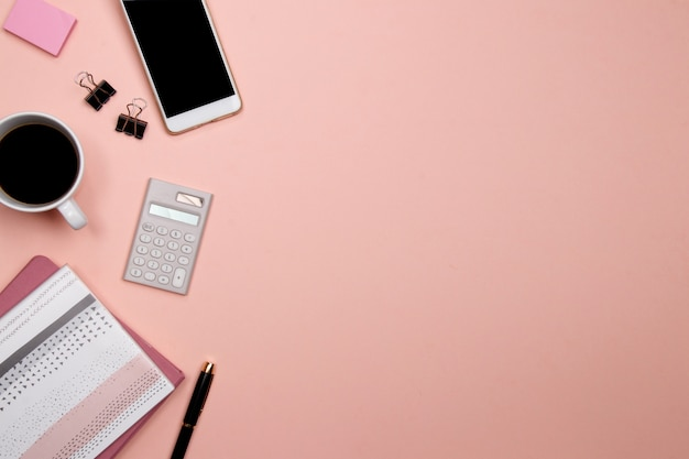 Biurowy stołowy biurko z smartphone i innymi biurowymi dostawami na różowym tle.
