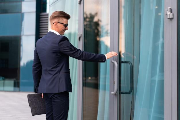 Biznes. biznesmen człowiek sukcesu osoba biznesu otwarte drzwi mała firma nowe możliwości kaukaski profesjonalny biznesmen dokumenty folder bank pracownik otwarte drzwi koncepcja uruchomienia wywiad