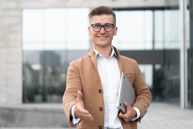Biznes. biznesmen dając dłoń na gest powitalny uścisk dłoni dorosły kaukaski mężczyzna biznes osoba trzymająca zamknięty laptop dać gotowy uścisk dłoni tło budynku biurowego