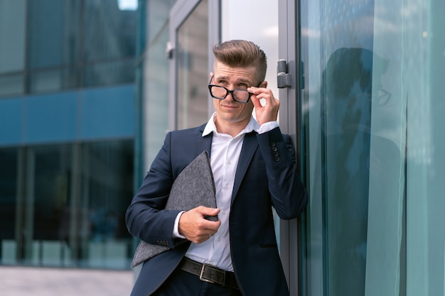 Biznes. biznesmen okulary z folderem stojący budynek biurowy wejście przystojny kaukaski mężczyzna biznes osoba portret miasto korporacyjny budynek tło udany młody dorosły kierownik