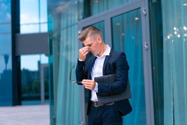 Biznes. biznesmen okulary z folderem stojący budynek biurowy wejście zmartwienia kryzys płacz pociera oczy kaukaski mężczyzna biznesmen miasto korporacyjny budynek tło kłopoty depresja bankructwo