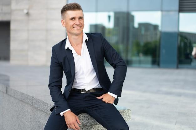 Biznes. biznesmen siedzi miasto ulica budynek biurowy przystojny kaukaski mężczyzna biznesmen portret korporacyjny budynek tło udany młody dorosły menedżer ubrany garnitur bez krawata