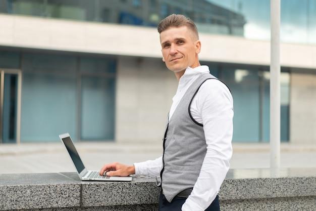 Biznes. biznesmen używa laptopa na zewnątrz. poważny zamyślony kaukaski mężczyzna biznesmen komputer poza nowoczesną koncepcją technologii młody dorosły menedżer myślenie kryzysowe kłopoty pomysł