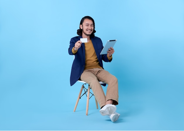 Biznes człowiek azjatycki szczęśliwy uśmiechnięty pokazując kartę kredytową i używając cyfrowego tabletu, siedząc na krześle na jasnoniebieskim.
