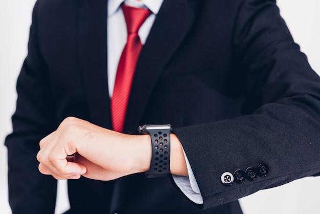 Biznes człowiek do noszenia, a on widzi inteligentny zegarek pod ręką,