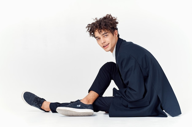 Biznes człowiek kręcone włosy zabawa garnitur siedzi na jasnym tle podłogi. wysokiej jakości zdjęcie