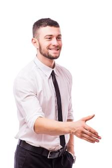 Biznes człowiek mówi witamy, podając rękę do uścisku, skup się na dłoni na białym tle na białej ścianie