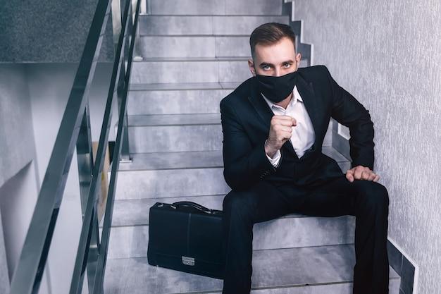 Biznes człowiek nosić maskę na twarz siedzieć na schodach
