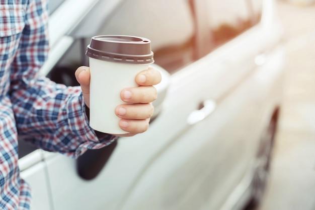 Biznes człowiek pije kawę na papierowy kubek obok swojego samochodu