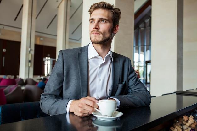 Biznes człowiek pije kawę w kawiarni - czas kawy