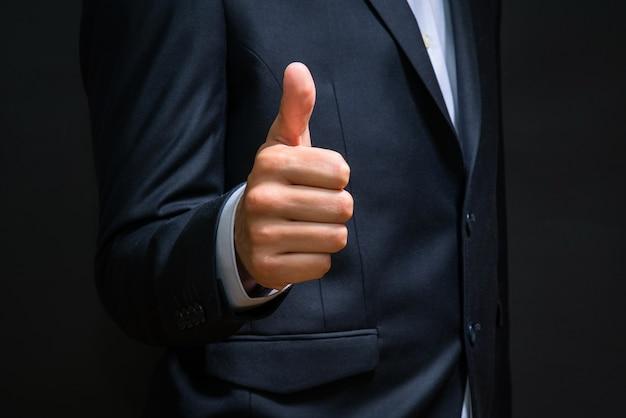 Biznes człowiek pokazuje kciuk znak gest. udana transakcja.