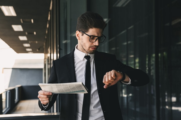 Biznes człowiek posiadający gazetę patrząc na zegarek zegar.