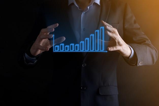 Biznes człowiek posiadający holograficzne wykresy i statystyki giełdowe zyskuje. koncepcja planowania rozwoju i strategii biznesowej. wyświetlacz dobrej ekonomii na ekranie cyfrowym.