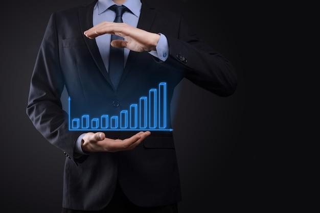 Biznes człowiek posiadający holograficzne wykresy i statystyki giełdowe zyskuje zyski