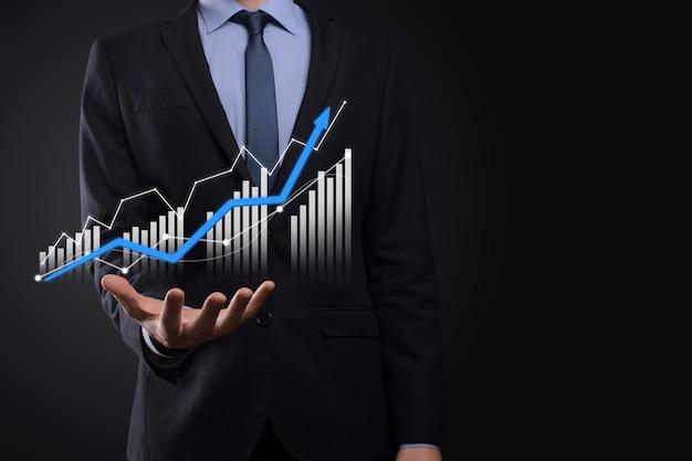 Biznes człowiek posiadający holograficzne wykresy i statystyki giełdowe zyskuje zyski.