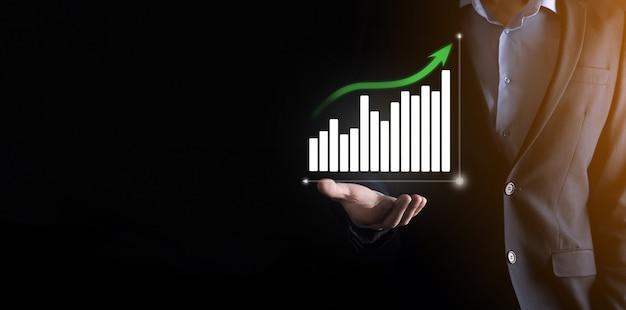 Biznes człowiek posiadający holograficzne wykresy i statystyki giełdowe zyskuje.