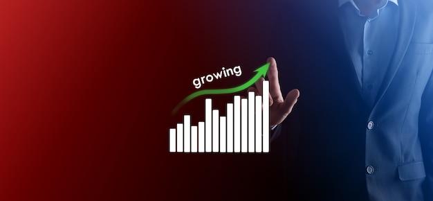 Biznes człowiek posiadający holograficzne wykresy i statystyki giełdowe zyskuje