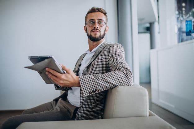 Biznes człowiek pracuje na tablecie i siedzi na kanapie