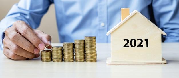 Biznes człowiek ręcznie kładąc złotą monetę na rosnących schodach pieniędzy z 2021 r