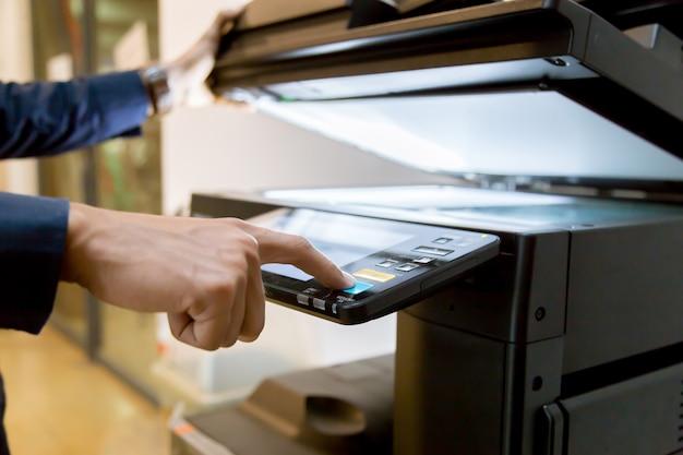 Biznes człowiek ręcznie naciśnij przycisk na panelu drukarki.