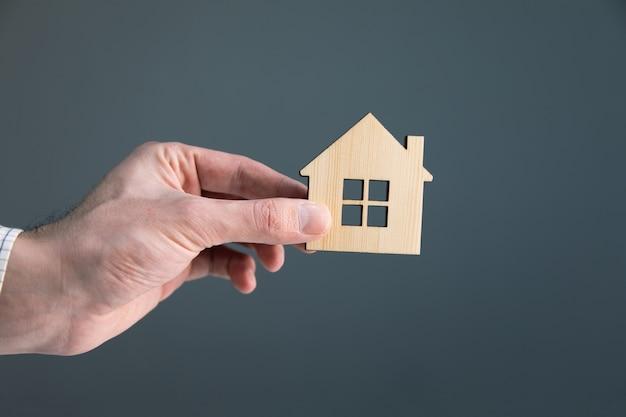 Biznes człowiek ręka trzyma drewniany dom