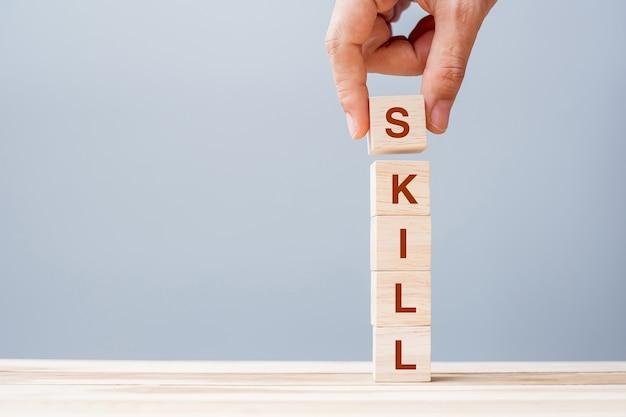 Biznes człowiek ręka trzyma drewniany sześcian blok słowem biznesu umiejętności na tle stołu. koncepcje uczenia się, wiedzy, nauki, szkolenia i doświadczenia