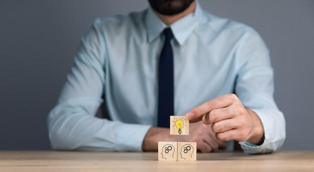 Biznes człowiek ręka żarówka na drewnianych kostkach