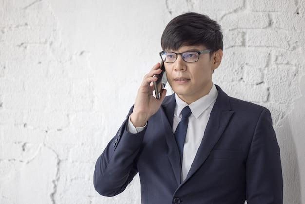 Biznes człowiek rozmawia przez telefon z białym tłem ściany cegła.