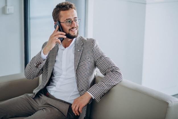 Biznes człowiek siedzi na kanapie i przy użyciu telefonu