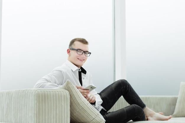 Biznes człowiek siedzi na kanapie w swoim salonie. ludzie i technologia