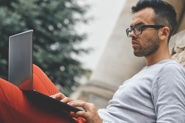 Biznes człowiek siedzi na ławce i ogląda na laptopie w parku miejskim na świeżym powietrzu