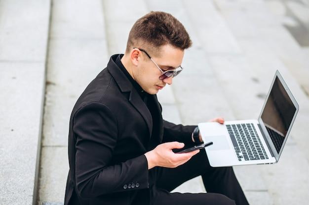 Biznes człowiek siedzi na schodach poza biurem, pracuje na komputerze przenośnym, dzwoniąc na telefon. stylowy model męski w czarnej kurtce. młody człowiek z telefonu komórkowego siedzi na schodach