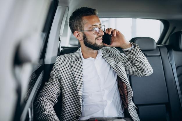 Biznes człowiek siedzi na tylnym siedzeniu samochodu za pomocą tabletu