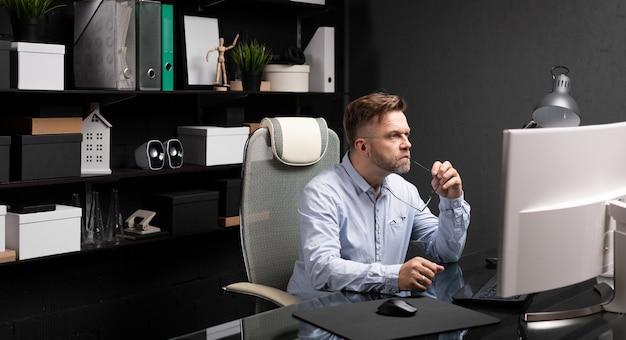 Biznes człowiek siedzi w biurze przy komputerze biurko i trzymając kajdanę ustach okulary