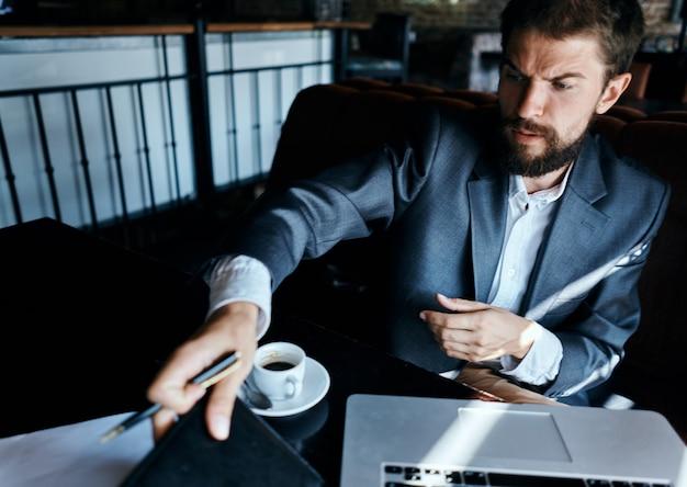 Biznes człowiek siedzi w kawiarni przed laptopem przy filiżance kawy styl życia technologii pracy