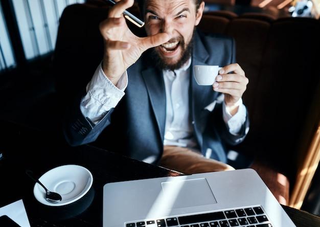 Biznes człowiek siedzi w kawiarni przed laptopem przy filiżance kawy styl życia technologii pracy.