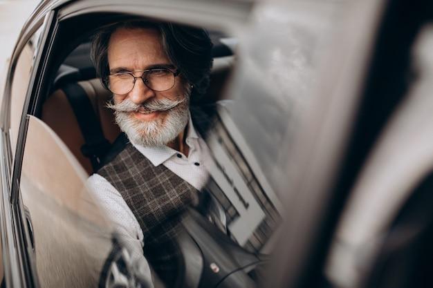 Biznes człowiek siedzi w swoim samochodzie na tylnym siedzeniu