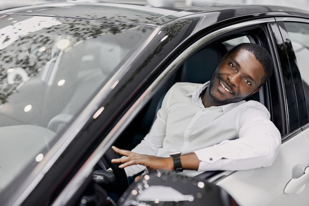 Biznes człowiek siedzi wewnątrz drogiego luksusowego samochodu w salonie