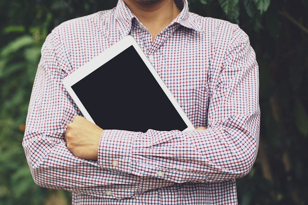 Biznes człowiek stoisko przytulić tablet. lub uczniowie przygotowują się do nauki.