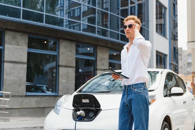 Biznes człowiek stojący w pobliżu ładowania samochodu elektrycznego i za pomocą tabletu na ulicy.