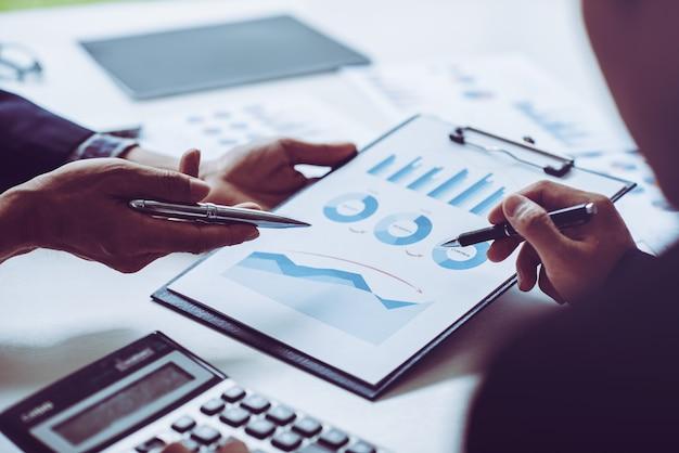 Biznes człowiek strony omawianie wykresu biznesowego, dłoń trzymająca pióro i rozmawiać z kolegami w biurze.