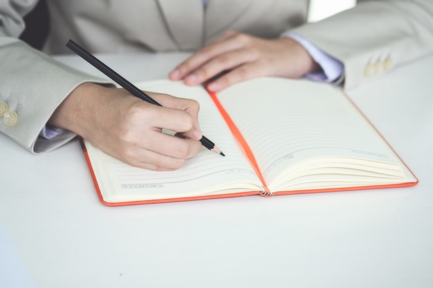 Biznes człowiek strony pisania w notatniku za pomocą pióra w biurze pracy.