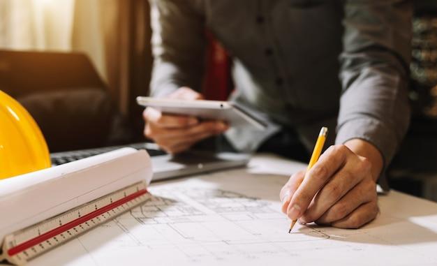 Biznes człowiek strony pracy i laptopa z na projekt architektoniczny na budowie przy biurku w biurze