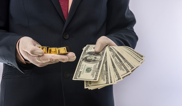 Biznes człowiek trzyma dolara i sztabkę złota w rękawiczkach medycznych dla bezpieczeństwa. kryzys covid19