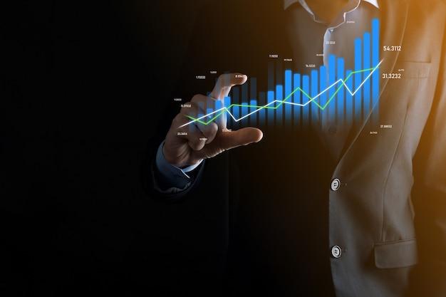 Biznes człowiek trzyma i pokazuje holograficzne wykresy i statystyki giełdowe zyskuje. koncepcja planowania rozwoju i strategii biznesowej. wyświetlacz dobrej ekonomii na ekranie cyfrowym.