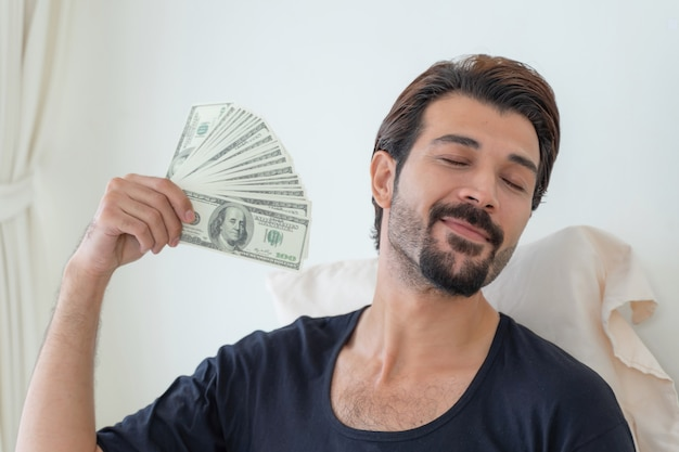 Biznes człowiek trzyma pieniądze rachunki w dolarach amerykańskich w biurze domowym