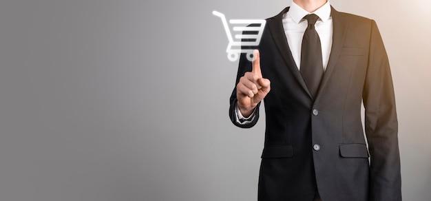 Biznes człowiek trzymać w ręku ikonę koszyka na zakupy. zakupy online concept.basket hologram. zakupy online, aplikacja sklepu internetowego w smartfonie. marketing cyfrowy online